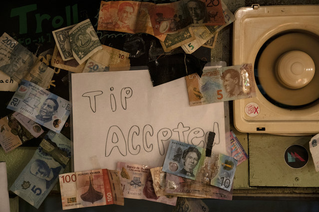 A sign is posted on the wall clustered with bills from various countries in a bar at the Golden Gai in the Shinjuku district of Tokyo, July 17, 2019. (Photo by Jae C. Hong/AP Photo)