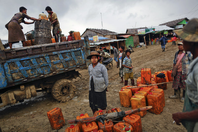 People wait to sell their crude oil to buyers at an oil field in the Minhla township of the Magwe district October 27, 2013. In Myanmar, an impoverished country rich with natural resources, people from poor communities find ways to supplement their income by exploiting such resources, such as the Minhla township, traditionally rich with oil, often using primitive and dangerous methods. (Photo by Damir Sagolj/Reuters)