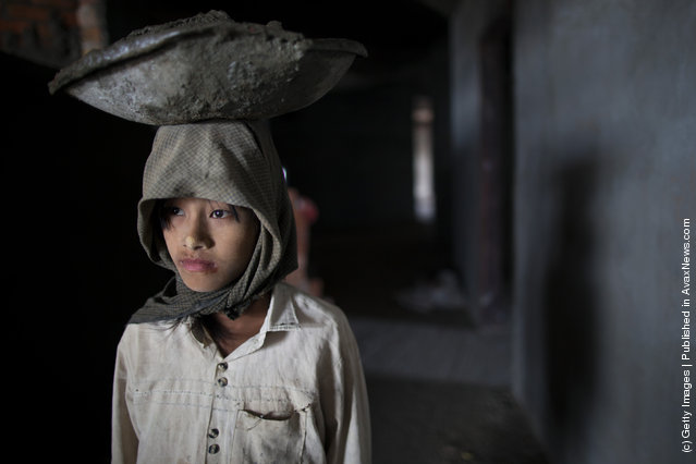 A Burmese girl carries cement on her head as she works at a construction site for a new hotel