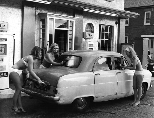 Four bikini-clad salesgirls brave near-freezing conditions to provide full service to a car at a garage in Ealing West London. Promoting European Petroleum, they are, from left to right: Stella Long, 22, Marilyn Woolhead (Miss E.P. Bikini 1965), 18 and Karen Lewis, 18. 30th November 1965. (Photo by Fox Photos/Getty Images)