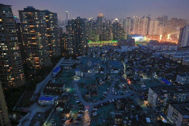 A night view of the old houses surrounded by new apartment buildings at Guangfuli neighbourhood in Shanghai, China, April 10, 2016. In a corner of Shanghai, surrounded by a cement wall, lies one of the world's most valuable fields of debris and garbage. On paper, the Guangfuli neighbourhood is a real estate investor's dream: a plot in the middle of one of the world's most expensive and fast-rising property markets. But the reality is more like a developer's nightmare, thanks to hundreds of people living there who have refused to budge from their ramshackle homes for nearly 16 years as the local authority sought to clear the land for new construction. (Photo by Aly Song/Reuters)