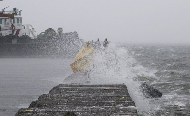 Residents walk along the breakwater as high waves brought by typhoon Linfa, locally named Egay, crash along Manila Bay at a slum area in Baseco, Tondo in Manila July 6, 2015. (Photo by Romeo Ranoco/Reuters)
