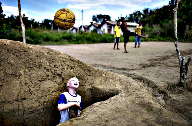 Maicon de Jesus Dias throws a ball he recovered from an open grave while playing soccer with in a makeshift field in a local cemetery of the city of Una, Bahia state, April 29, 2014. Brazil will host the 2014 World Cup starting June 12. (Photo by Roosevelt Cassio/Reuters)