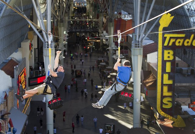 """Russ Dostal, left, gives a thumbs up as he tries the new 850-foot-long SlotZilla Zipline with Tom Delaney at the Fremont Street Experience in downtown Las Vegas, on April 30, 2014. A higher and longer 1,700-foot Zoomline, which will propel flyers in a horizontal """"superman"""" position at speeds up to 35 mph, is expected to open in June. The zip line, part of the $12 million SlotZilla project, opened Sunday. (Photo by Steve Marcus/Las Vegas Sun via Reuters)"""