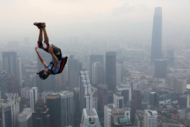 A BASE jumper leaps from Kuala Lumpur Tower on a hazy day during International Jump Malaysia 2019 in Kuala Lumpur, Malaysia, September 26, 2019. (Photo by Lim Huey Teng/Reuters)