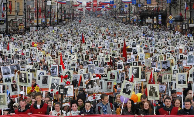 """Local residents carry portraits of their ancestors, participants in World War Two as they celebrate Victory Day in St. Petersburg, Russia, Friday, May 9, 2014. About 30,000 people walked in central streets in a march named """"Immortal regiment"""" while carrying portraits their relatives who fought in World War Two. Victory Day, marking the defeat of Nazi Germany, is Russia's most important secular holiday, celebrated on May 9. (Photo by Dmitry Lovetsky/AP Photo)"""