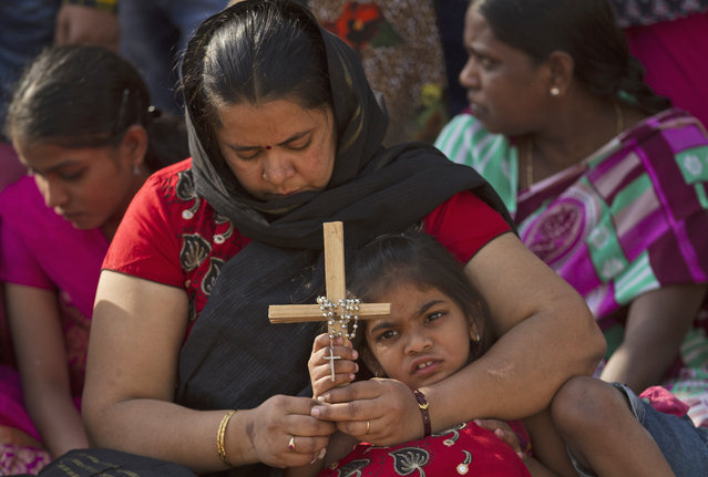 An Indian mother and daughter pray as they watch the reenacting of the crucifixion of Jesus Christ during Good Friday in Hyderabad, India, Friday, April 14, 2017. Christians around the world are marking the solemn period of Easter. (Photo by Mahesh Kumar A./AP Photo)