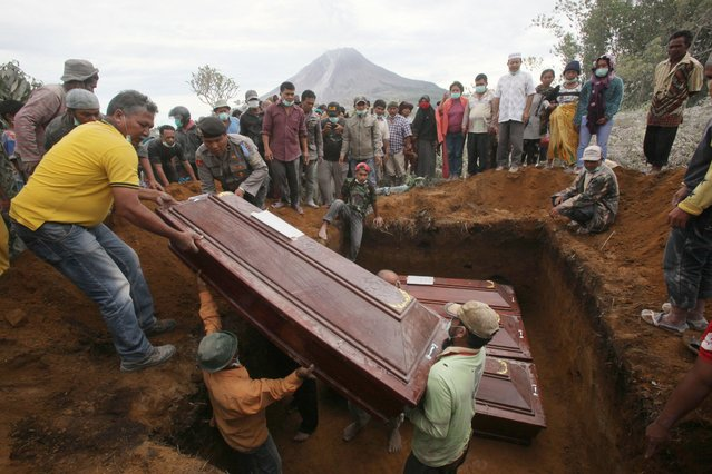 Coffins containing the bodies of the victims in the eruption of Mount Sinabung are lowered into a grave during a funeral in Sukandebi, North Sumatra, Indonesia, Sunday, May 22, 2016. (Photo by Binsar Bakkara/AP Photo)