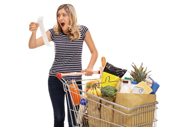 Shocked young woman looking at a store receipt. (Photo by Dreamstime/Getty Images)