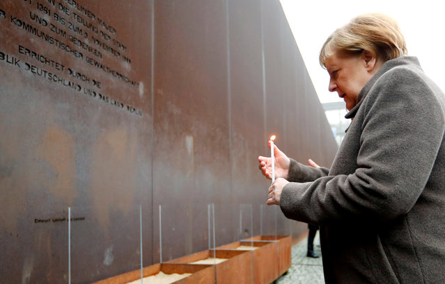 German Chancellor Angela Merkel lights a candle at the memorial of the divided city and the victims of communist tyranny during a ceremony marking the 30th anniversary of the fall of the Berlin Wall at the Wall memorial on Bernauer Strasse in Berlin, Germany, November 9, 2019. (Photo by Fabrizio Bensch/Reuters)