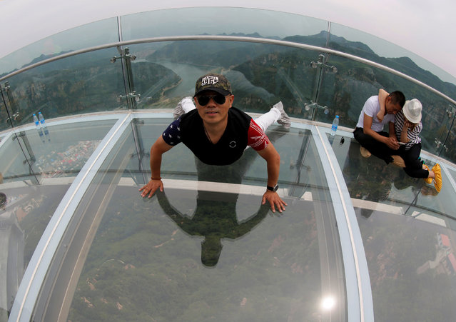 A man poses for his souvenir picture on the glass sightseeing platform on Shilin Gorge in Beijing, China, May 27, 2016. (Photo by Kim Kyung-Hoon/Reuters)