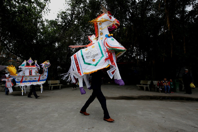 A man carries a paper horse which will be offered to saints before a ritual Hau Dong ceremony at Lanh Giang temple, in Ha Nam province, Vietnam, March 26, 2017. (Photo by Reuters/Kham)