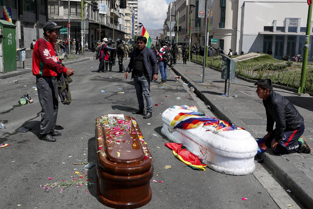 Coffins containing the remains of people killed during clashes between security forces and supporters of former President Evo Morales, lay in the middle of a street after police launched tear gas at a massive funeral procession to disperse anti-government protesters accompanying the coffins into La Paz, Bolivia, Thursday, November 21, 2019. Bolivia has been in a state of turbulence since Morales resigned Nov. 10 after weeks of protests against him over a disputed vote that, according to an international audit, was marred by irregularities. (Photo by Juan Karita/AP Photo)