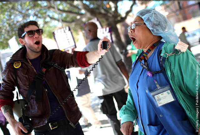 Nurse Inez Banks (R) yells into a megaphone as she protests outside of San Francisco General Hospital
