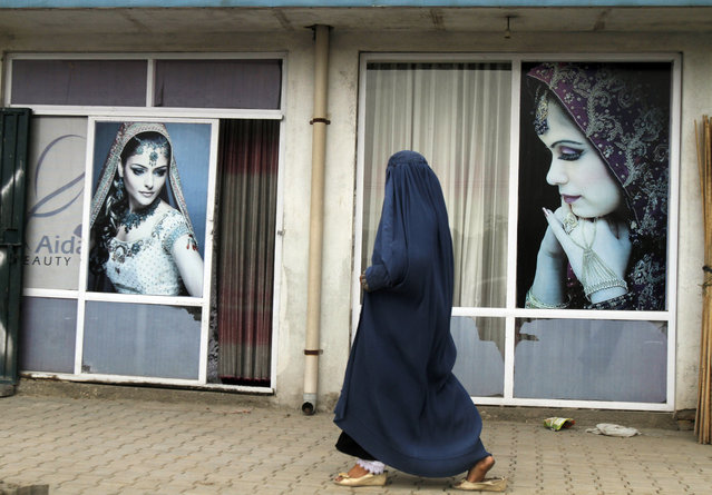 An Afghan woman wearing a Burqa, the all-covering dress worn by some Muslim women, walks past a beauty shop in, Kabul, Afghanistan, Monday, May 4, 2015. (Photo by Allauddin Khan/AP Photo)