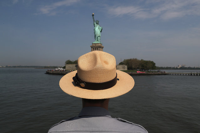 A U.S. park ranger looks towards the Statue of Liberty while in route to Ellis Island on May 27, 2016 in New York City. U.S. Secretary of Homeland Security Jeh Johnson visited the historic island to administer the oath of citizenship to immigrants from 39 countries. The ceremony, held by U.S. Citizenship and Immigration Services (USCIS), was held in honor of Memorial Day and is one of 100 naturalization ceremonies held in U.S. national parks in celebration of the National Park Service's 100th anniversary. (Photo by John Moore/Getty Images)