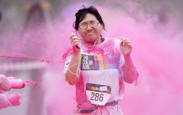 A woman reacts as she is sprayed with colour powder during a five-kilometre colour run event in Beijing June 21, 2014. (Photo by Reuters/China Daily)