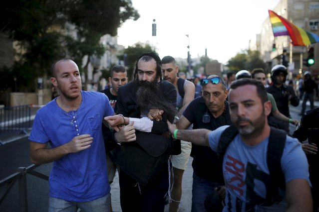 People detain after disarming an Orthodox Jewish assailant, after he stabbed and injured six participants of an annual gay pride parade in Jerusalem on Thursday, police and witnesses said July 30, 2015. (Photo by Amir Cohen/Reuters)