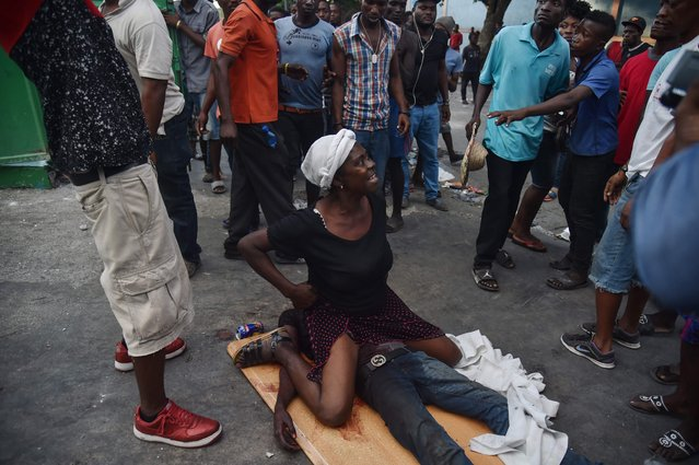 A mother in shock cries while sitting on the body of her dead son who was shot during clashes between Haitian police and demonstrators near to the National Palace in Port-au-Prince, on February 9, 2019. Demonstrators are demanding the resignation of Haitian President Jovenel Moise and protesting the Petrocaribe fund which for years Venezuela supplied Haiti and other Caribbean and Central American countries with oil at cut-rate prices and on easy credit terms. But investigations by the Haitian Senate in 2016 and 2017 concluded that nearly $2 billion from the program was misused. (Photo by Hector Retamal/AFP Photo)