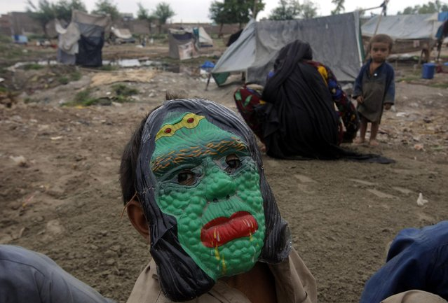 A boy wearing a mask sits with his family after being displaced by heavy rains in a suburb of Peshawar, Pakistan, Thursday, July 23, 2015. The country's military has deployed helicopters and boats Wednesday to evacuate flood victims, as 285,000 have been affected by monsoon rains and flash floods in and around the city of Chitral in Pakistan's Khyber Pakhtunkhwa province, according to the National Disaster Management Authority. (Photo by Mohammad Sajjad/AP Photo)