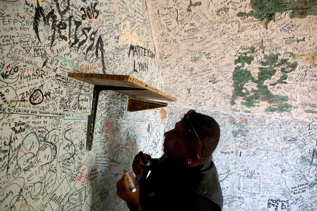 Daniel Shorts, of Rhode Island, signs his name on a wall  at the Stone House Saloon outside of Belle Fourche, South Dakota, while participating in the annual Sturgis Motorcycle Rally in South Dakota, August 5, 2015. (Photo by Kristina Barker/Reuters)