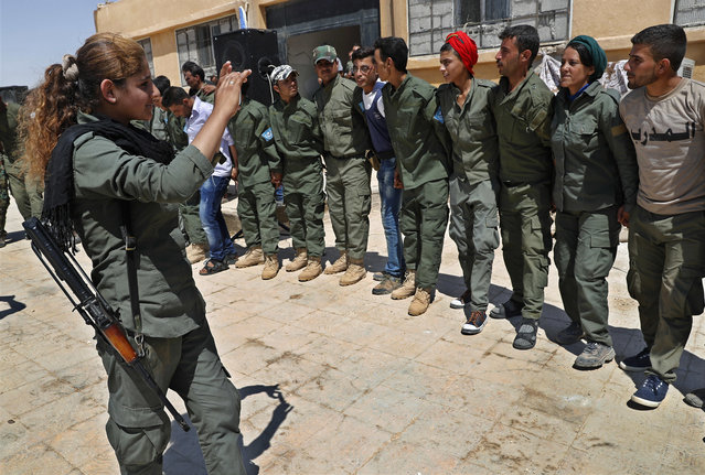 Syrian Internal Security Forces dance in celebration during their graduation ceremony, at Ain Issa desert base, in Raqqa province, northeast Syria, Thursday, July 20, 2017. Some 250 residents of Syria's Raqqa province are the latest batch to graduate from a brief U.S-training course that is preparing an internal security force to hold and secure areas as they are captured from Islamic State militants. (Photo by Hussein Malla/AP Photo)