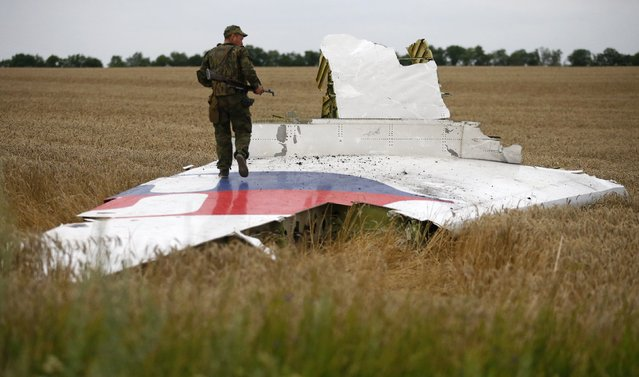 An armed pro-Russian separatist stands on part of the wreckage of the Malaysia Airlines Boeing 777 plane after it crashed near the settlement of Grabovo in the Donetsk region, July 17, 2014. The Malaysian airliner flight MH-17 was brought down over eastern Ukraine on Thursday, killing all 295 people aboard and sharply raising stakes in a conflict between Kiev and pro-Moscow rebels in which Russia and the West back opposing sides. (Photo by Maxim Zmeyev/Reuters)