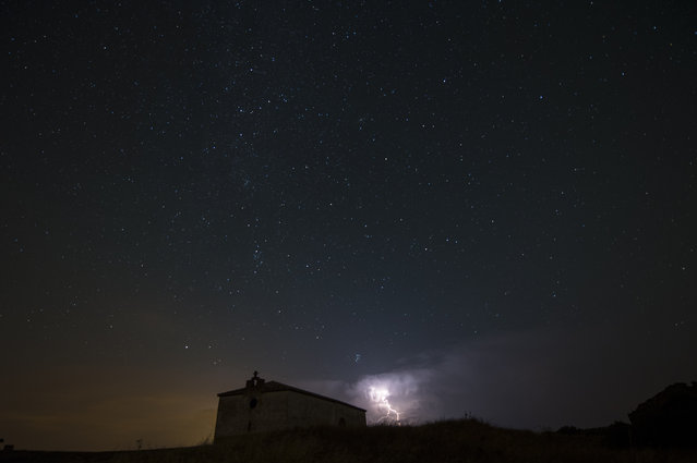 Stars and storm seen as streaks from a long camera exposure are seen behind an ancient Hermitage, in Murillo del Fruto, northern Spain,  Wednesday, August 12, 2015. The meteor shower is expected to peak Wednesday night into Thursday morning. (Photo by Alvaro Barrientos/AP Photo)
