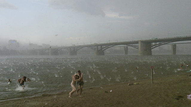In this photo taken on a smartphone on Saturday, July  12, 2014, people run to shelter from hailstorm on the beach at Ob River, the major river in western Siberia in Novosibirsk, Russia. The Investigative Committee said in a statement published online Monday that two young girls aged three and four had died Saturday in the lakeside town of Bredsk, not far from the large Siberian city of Novosibirsk. (Photo by Nikita Dudnik/AP Photo)