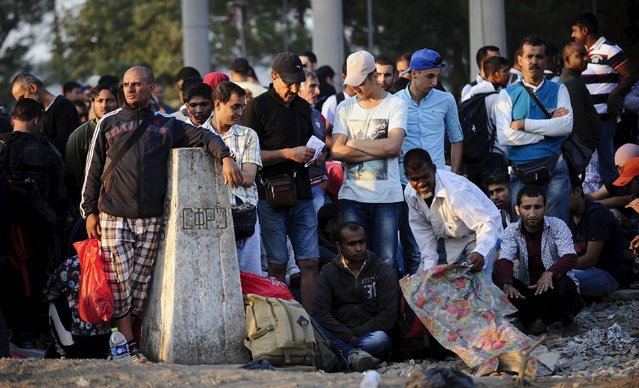 People, part of a new group of more than a thousand immigrants, gather near a Yugoslavia border stone, as they wait at the border line of Macedonia and Greece to enter into Macedonia  near Gevgelija railway station August 20, 2015. (Photo by Ognen Teofilovski/Reuters)