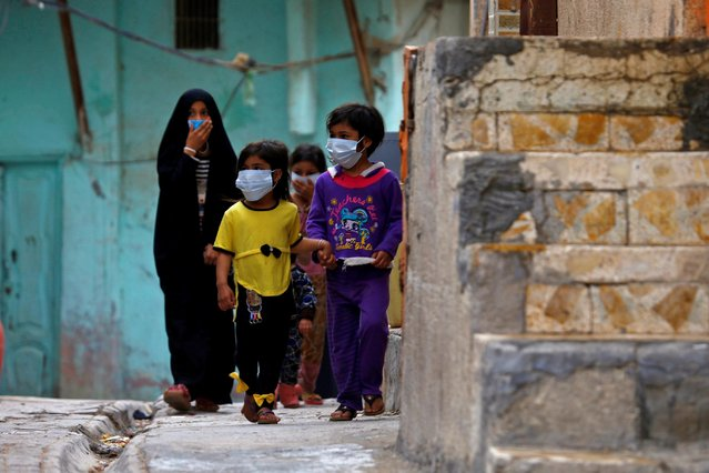 Iraqi children wear protective masks as they walk near a religious school where the first coronavirus case was detected, following the outbreak of the coronavirus, in the holy city of Najaf, Iraq, February 24, 2020. (Photo by Alaa al-Marjani/Reuters)