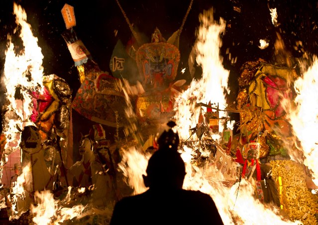 """An Ethnic Chinese priest stands in front of statue made of paper of Chinese deity """"Da Shi Ye"""" or Guardian God of Ghosts set of fire by devotees during the Hungry Ghost festival in Kuala Lumpur, late on August 10, 2014. (Photo by Manan Vatsyayana/AFP Photo)"""