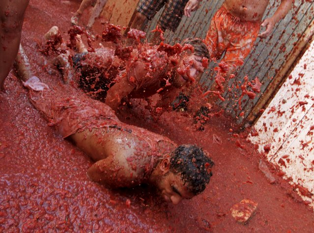 """Revelers play in tomato pulp after the annual """"Tomatina"""" (tomato fight) in Bunol, near Valencia, Spain, August 26, 2015. (Photo by Heino Kalis/Reuters)"""