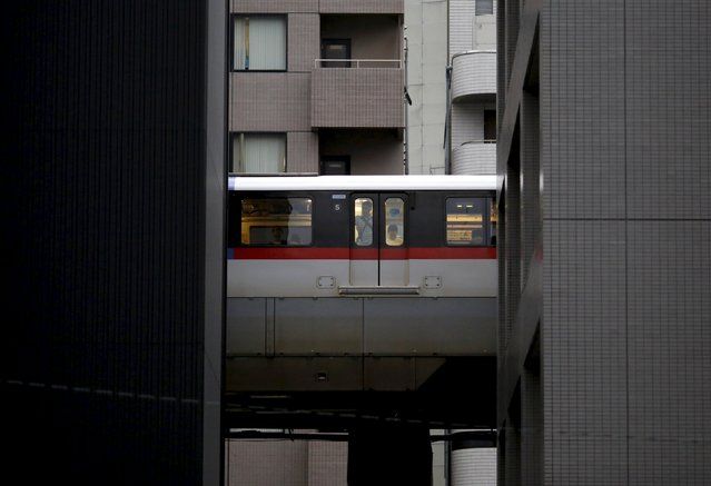 A man looks through a window of a monorail as it travels past  office buildings in Tokyo August 26, 2015. (Photo by Toru Hanai/Reuters)
