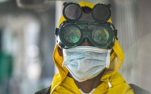 A cleaning staff waers protective gear to disinfect a metro carriage as a prevemtive measure against the spreading of the COVID-19 coronavirus in Addis Ababa, Ethiopia, on March 20, 2020. African countries have been among the last to be hit by the global COVID-19 coronavirus epidemic but as cases rise, many nations are now taking strict measures to block the deadly illness. (Photo by Michael Tewelde/AFP Photo)