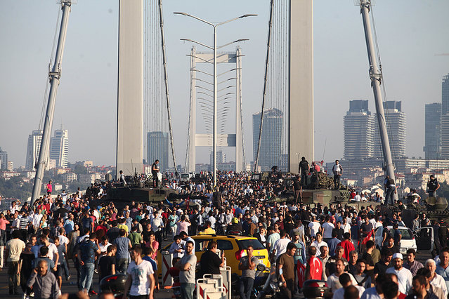 People gather for celebration around Turkish police officers, loyal to the government, standing atop tanks abandoned by Turkish army officers, against a backdrop of Istanbul's iconic Bosporus Bridge on July 16, 2016 in Istanbul, Turkey. (Photo by Burak Kara/Getty Images)