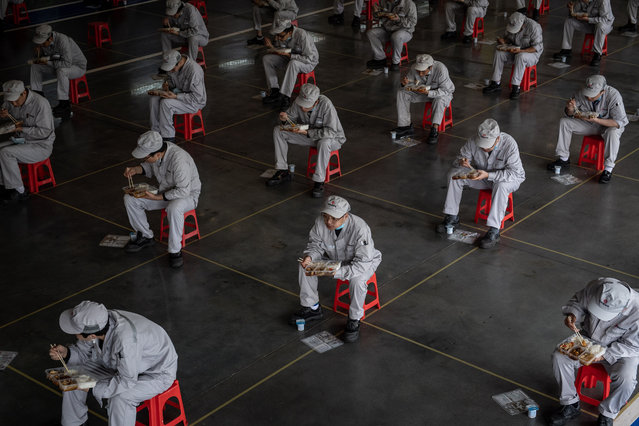 Workers have lunch while sitting 1.5 meters away from others at the joint-venture Dongfeng Honda in Wuhan, Hubei province, China, 23 March 2020 (issued 24 March 2020). The automaker says 95 percent of its labor force has returned to their posts after the long COVID-19 break. (Photo by Yi Xin/EPA/EFE)