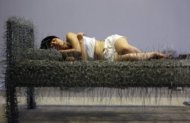 "Chinese artist Zhou Jie takes a nap on an unfinished iron wire bed, one of her sculpture works, after lunch at Beijing Now Art Gallery, in Beijing August 11, 2014. Zhou started her art project titled ""36 Days"" on August 9, in which she would live inside an exhibition hall with an unfinished iron wire bed, some iron wire sculptures in the shape of stuffed animal dolls, a certain amount of food and her mobile phone, for 36 days. (Photo by Jason Lee/Reuters)"