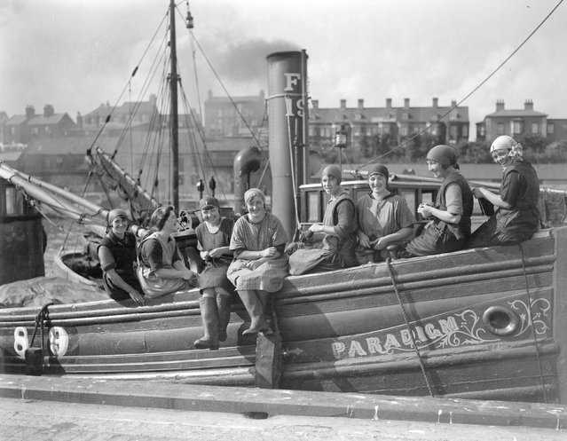 """A group of Scottish fisherwomen arrive at Great Yarmouth aboard the fishing vessel """"Paradigm"""" for the autumn herring season. The women busy themselves knitting while waiting for the boats to bring in the herring. 27th September 1928. (Photo by Harold Clements/London Express)"""