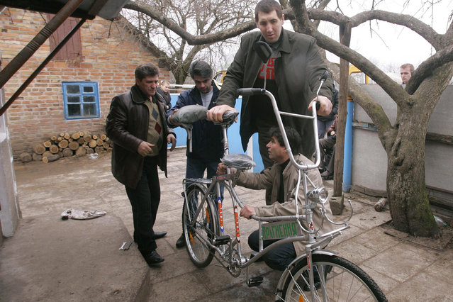 Ukrainian Leonid Stadnyk (R, standing) inspects a new bicycle specially made for him in the village of Podolyantsi in Ukraine's Zhytomyr region, about 200 km (124 miles) from the capital Kiev, March 23, 2008. Stadnyk, at 2.53 metres (8-foot, four-inch), is the world's tallest man according to the Guinness World Records. (Photo by Reuters/Stringer)