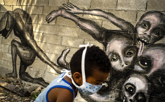 """A boy wearing a mask as a precaution against the spread of the new coronavirus plays in front of a mural by artist Yuriel Pena titled """"Marcha Hacia la Oscuridad"""", or Move Toward Darkness, in the patio of a home in Havana, Cuba, Friday, April 10, 2020. Pena said his latest murals show humanity's powerlessness against the COVID-19 disease. (Photo by Ramon Espinosa/AP Photo)"""