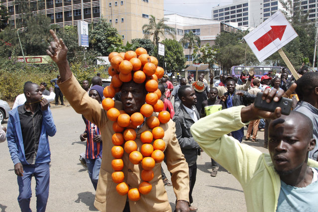 Supporters of opposition leader, Raila Odinga, one wearing oranges, the symbol the Democratic Party of Kenya, demonstrate in Nairobi, Kenya Tuesday, September 26, 2017. The protest is to demand the resignations of top officials of the Independent Electoral and Boundaries Commission following the annulment of presidential elections in August. Ruling party supporters also demonstrated calling for no change to the electoral body. (Photo by Khalil Senosi/AP Photo)