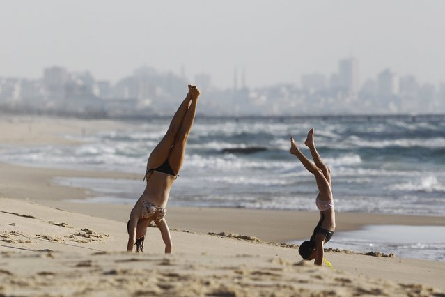 """Israeli girls play on Zikim beach at the Mediterranean sea as the northern Gaza Strip is seen in the background August 12, 2014. Talks to end a month-long war between Israel and Gaza militants are """"difficult"""", Palestinian delegates said on Tuesday, while Israeli officials said no progress had been made so far and fighting could soon resume. (Photo by Amir Cohen/Reuters)"""