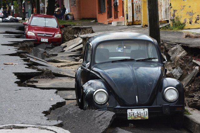 Cars are seen on a street damaged due to heavy rains in Veracruz September 2, 2014. Two separate tropical storms closed in on Mexico from both the Pacific and Atlantic Oceans on Tuesday, risking a double hit on the country a year after a pair of storms converged to cause major flooding that killed over 100 people. Tropical Storm Dolly, which formed in the southern Gulf of Mexico early Tuesday, is likely to strengthen slightly in the next 24 hours until it reaches the mainland, the U.S. National Hurricane Center (NHC) said. (Photo by Jonatan Rosas/Reuters)