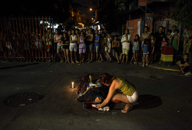 """Nanette Castillo looks at the dead body of her son Aldrin, an alleged drug user killed by unidentified assailants, in Manila on October 3, 2017. Philippines police officers who want to speak out about """"extrajudicial killings and summary executions"""" in President Rodrigo Duterte's drug war have been offered sanctuary and legal help by the Catholic Church. The Catholic Church, which counts 80 percent of Filipinos as followers, has been one of the leading critics of the drug war and its offer to police on Monday was another step in its efforts to stop the killings. (Photo by Noel Celis/AFP Photo)"""
