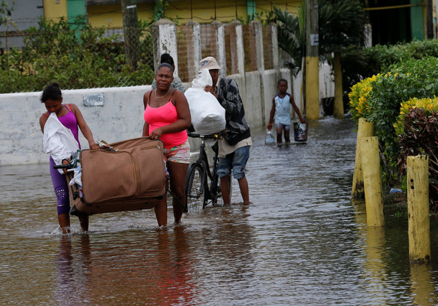 People carry their belongings as they leave a school used as a shelter, after Hurricane Earl hit, in Belize City, Belize August 4, 2016. (Photo by Henry Romero/Reuters)
