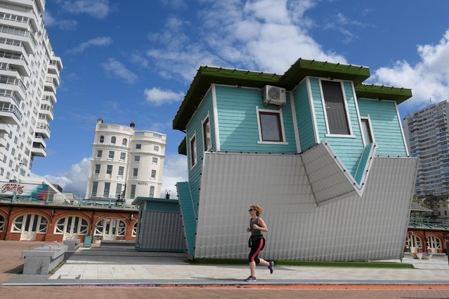 A woman runs past the upside down house along the seafront in Brighton, following the outbreak of the coronavirus disease (COVID-19), Brighton, Britain, May 14, 2020. (Photo by Toby Melville/Reuters)