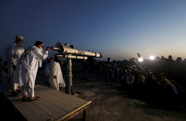 Members of the media (R) take pictures of Pakistan's moon sighting committee, as they use a telescope to look for the new moon that will mark the start of the holy month of Ramadan, amid spread of the coronavirus disease (COVID-19), from the Pakistan's Meteorological Department (PMD) building in Karachi, Pakistan ON April 23, 2020. (Photo by Akhtar Soomro/Reuters)