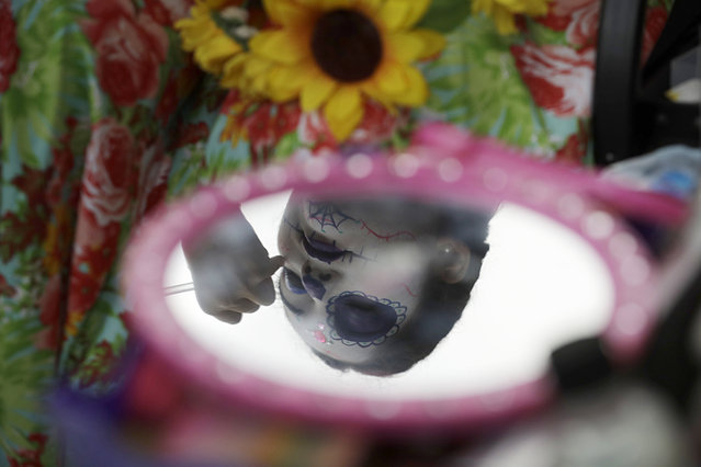 """A young woman gets her face painted in the style of Mexico's iconic """"Catrina"""" ahead of the start of the Grand Procession of the Catrinas, part of upcoming Day of the Dead celebrations in Mexico City, Sunday, October 22, 2017. (Photo by Rebecca Blackwell/AP Photo)"""
