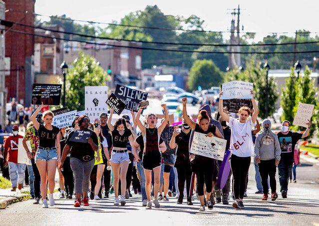"Protesters rally against the death in Minneapolis police custody of George Floyd in Anna, Illinois on June 4, 2020. Before sundown, around 150 protesters marched down the main street in Anna, past Bob's Tavern, Oasis of Grace Church, Douglas Skating Rink and Casey's General Store holding homemade signs and chanting ""black lives matter"". Nearly a century ago this southern Illinois town of 4,200 residents expelled most of its African-American residents, according to historians. (Photo by Brian Munoz/Reuters)"